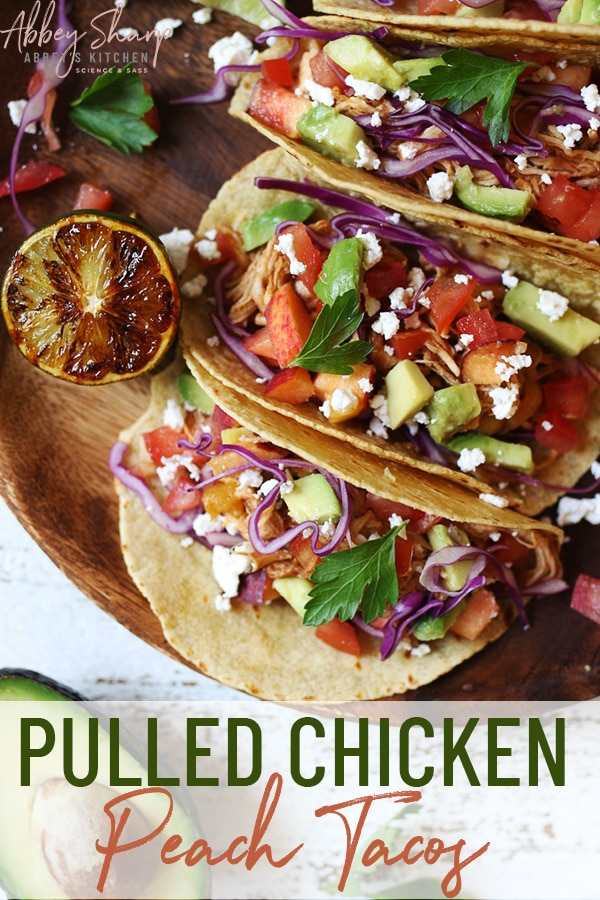 pinterest image of three peach barbecue chicken tacos served on a wooden plate garnished with lime, crumbled cheese, and fresh herbs