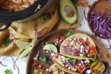 Chicken tacos on a wooden plate next to slow cooker with pulled chicken.
