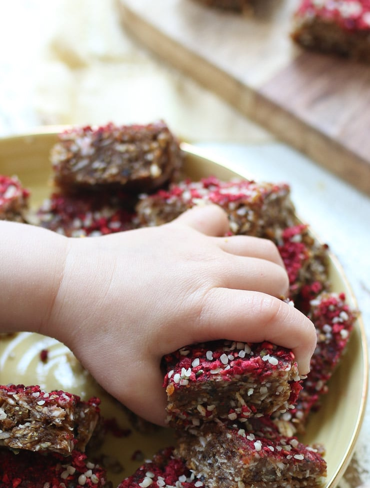 Baby's hand holding a homemade granola bar square.