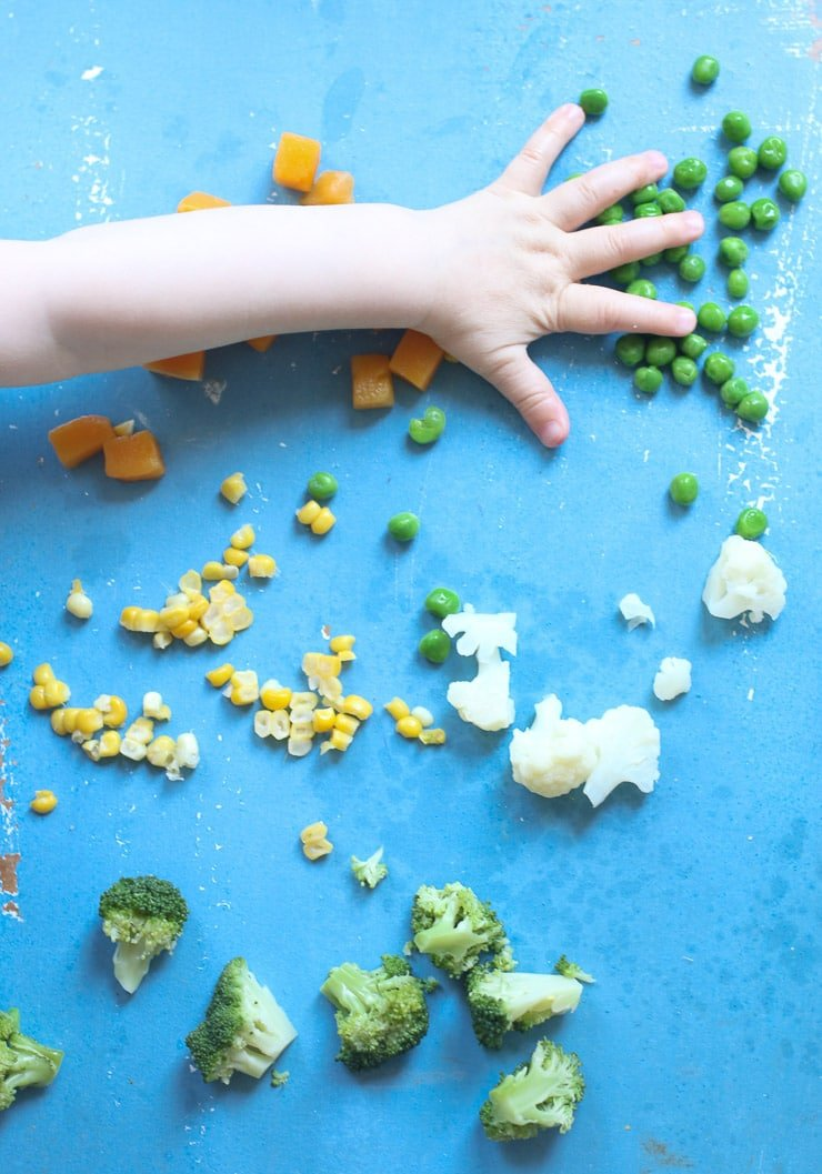 Baby's hand reaching for vegetables.