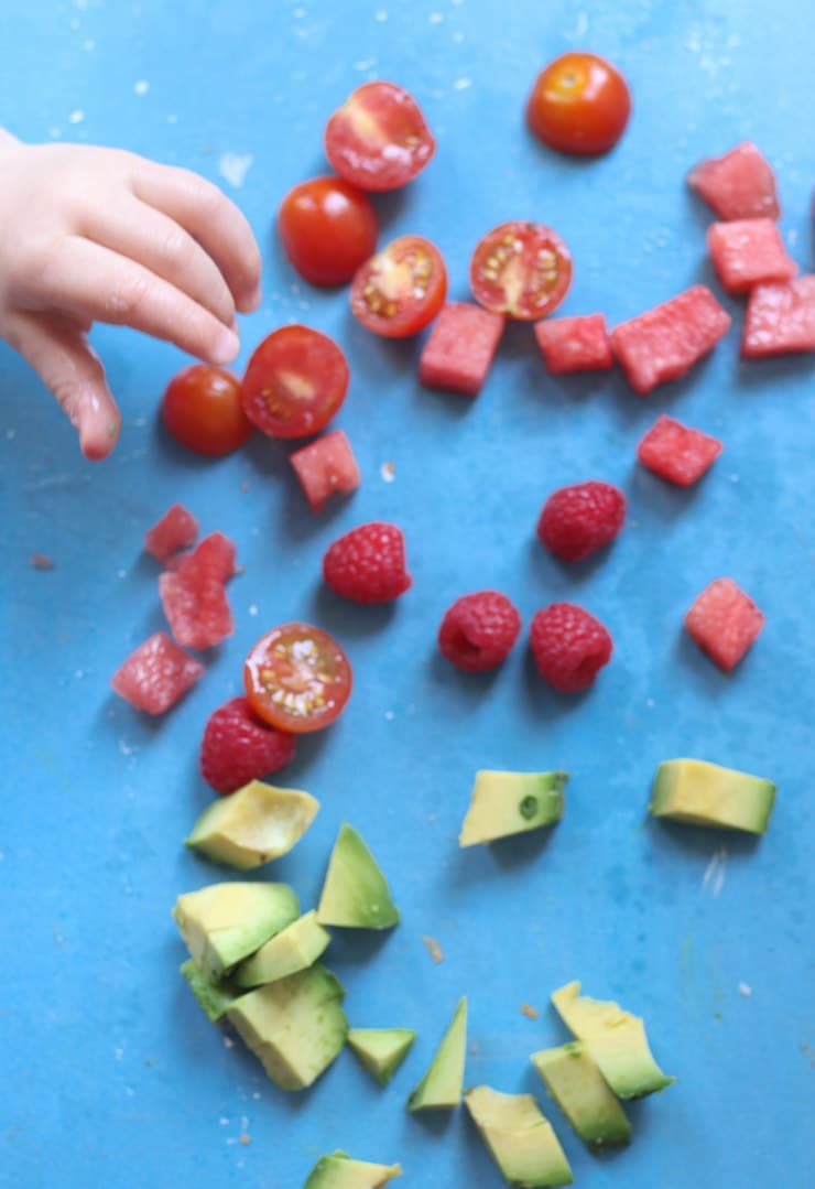 Baby's hand reaching for watermelon and tomatoes