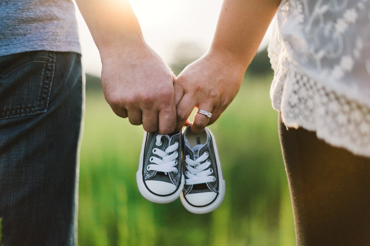 A couple holding one pair of baby shoes.