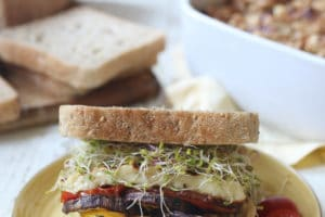 Veggie sandwich with hummus and halloumi served on a yellow plate.