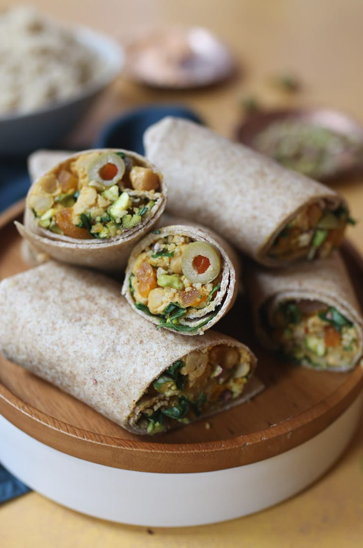 Moroccan chickpea salad wraps served on a wooden plate.