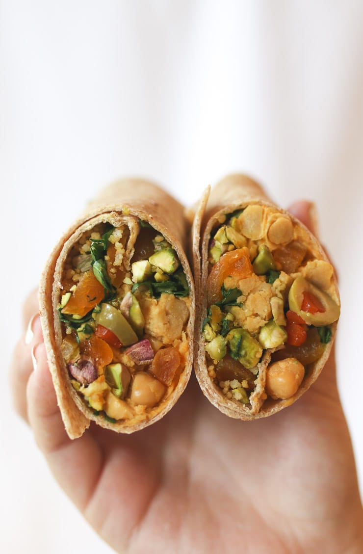 Hands holding moroccan chickpea salad wraps