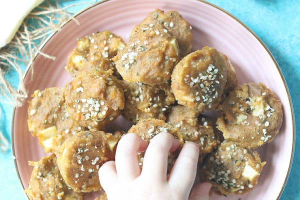 Toddler hand reaching for mini muffins from pink plate.