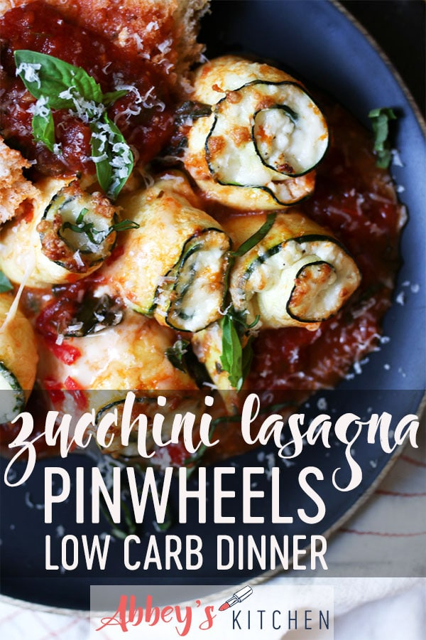 Zucchini lasagna pinwheel served on a black wooden plate.