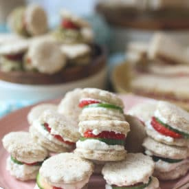 Strawberry and cucumber finger sandwiches on a pink plate.
