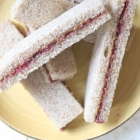 Peanut butter and jelly finger sandwiches on a yellow plate.