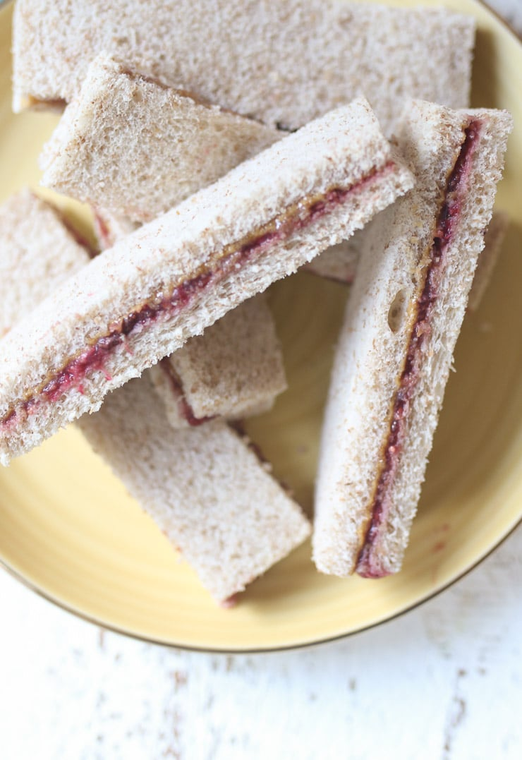 Peanut butter and jelly finger sandwiche on a yellow plate.
