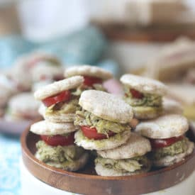 Chicken and pesto finger sandwiches on a wooden plate.