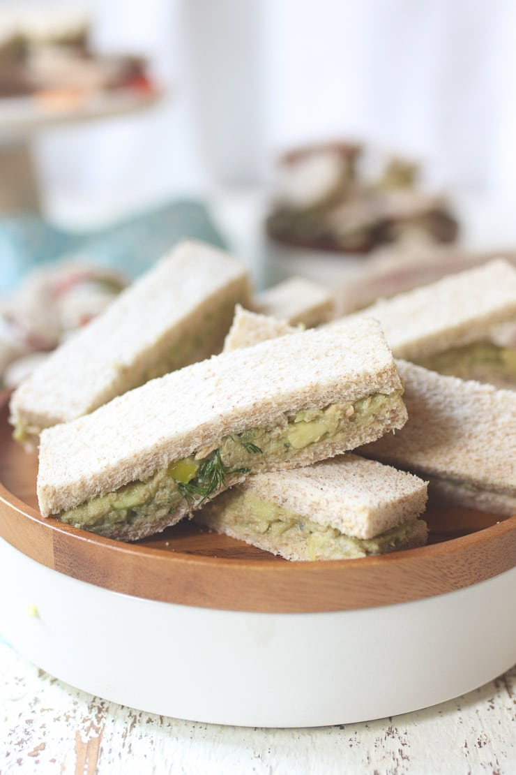 Avocado and salmon finger sandwiches on a wooden plate.
