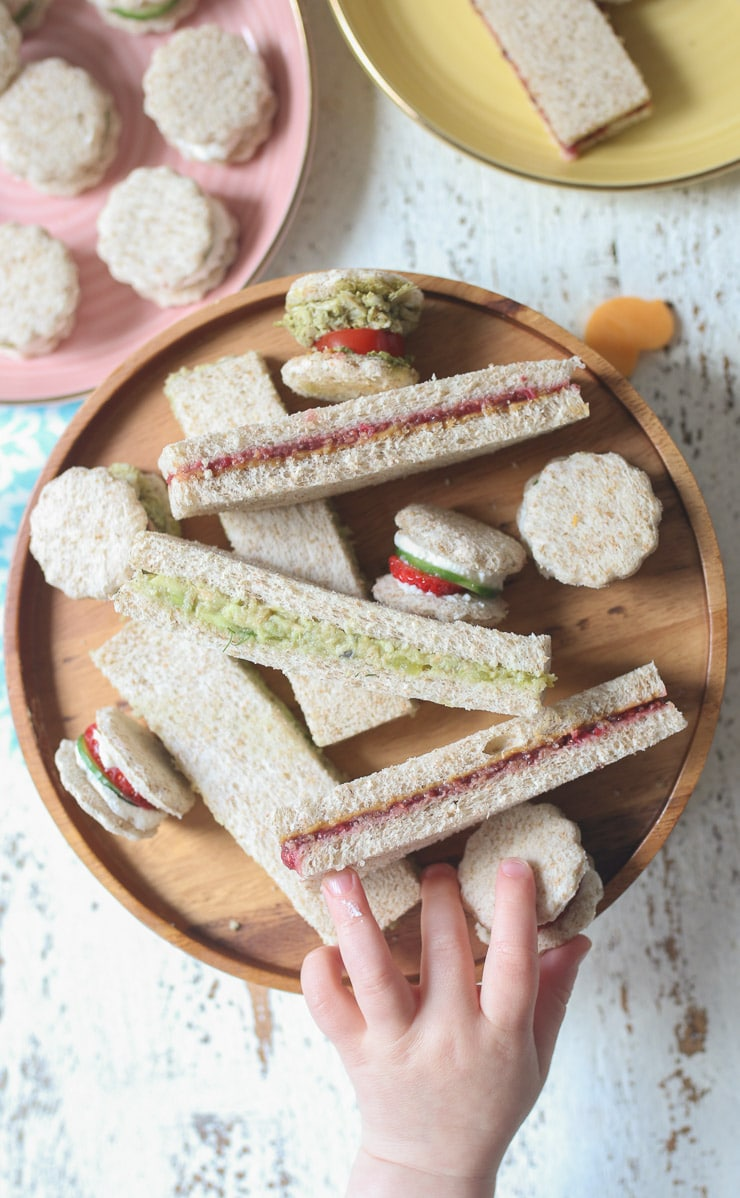Toddler hand reaching for a finger sandwich on a wooden plate.