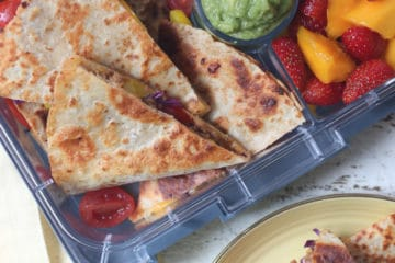 Quesadilla in a lunch box and served on a yellow plate.