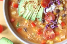 Tortilla soup in a large bowl topped with avocado and cabbage.