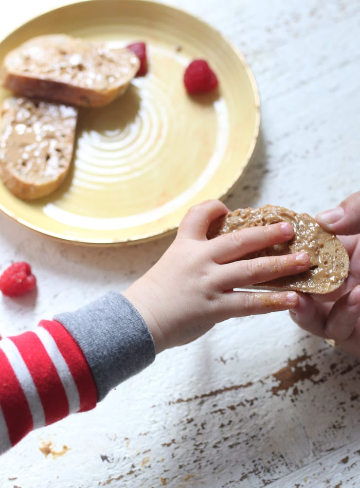 Baby's hand holding a piece of bread with peanut butter.