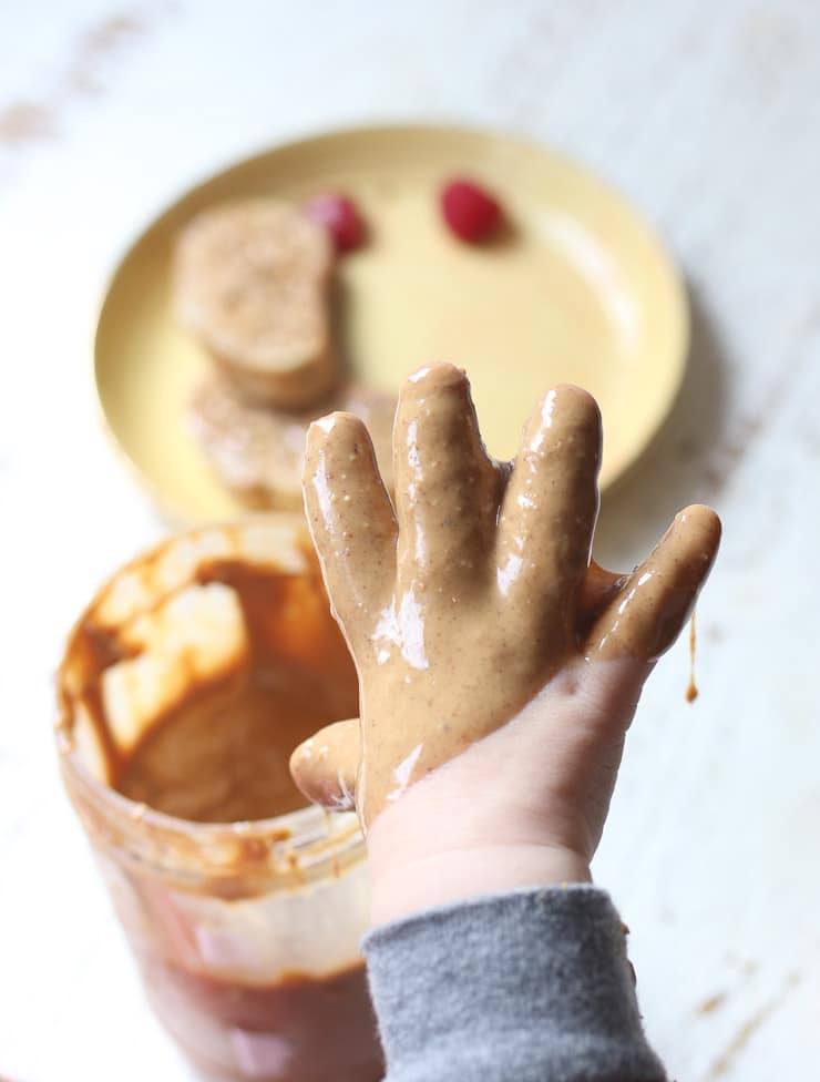 Baby's hand covered in peanut butter