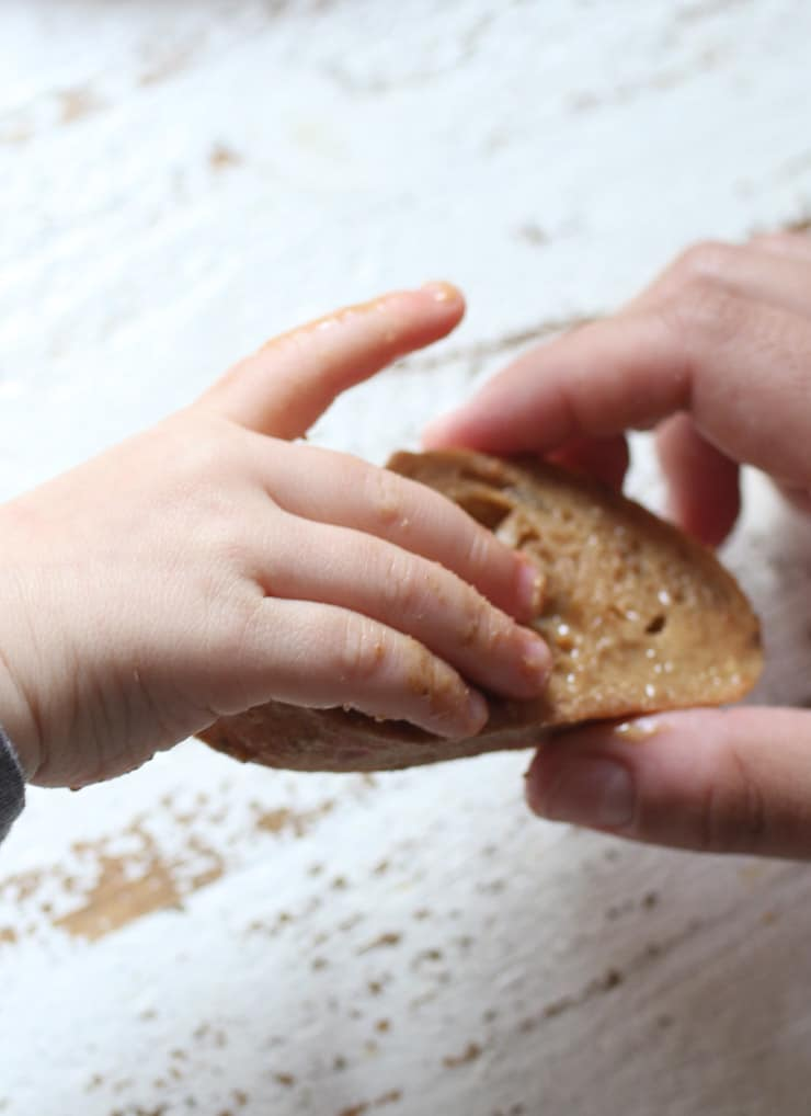 Baby's hand holding bread with peanut butter