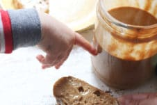 Baby's hand pointing to jar of peanut butter.
