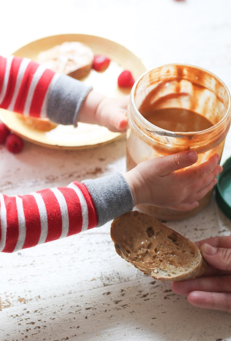 Baby's hand holding a jar of peanut butter.