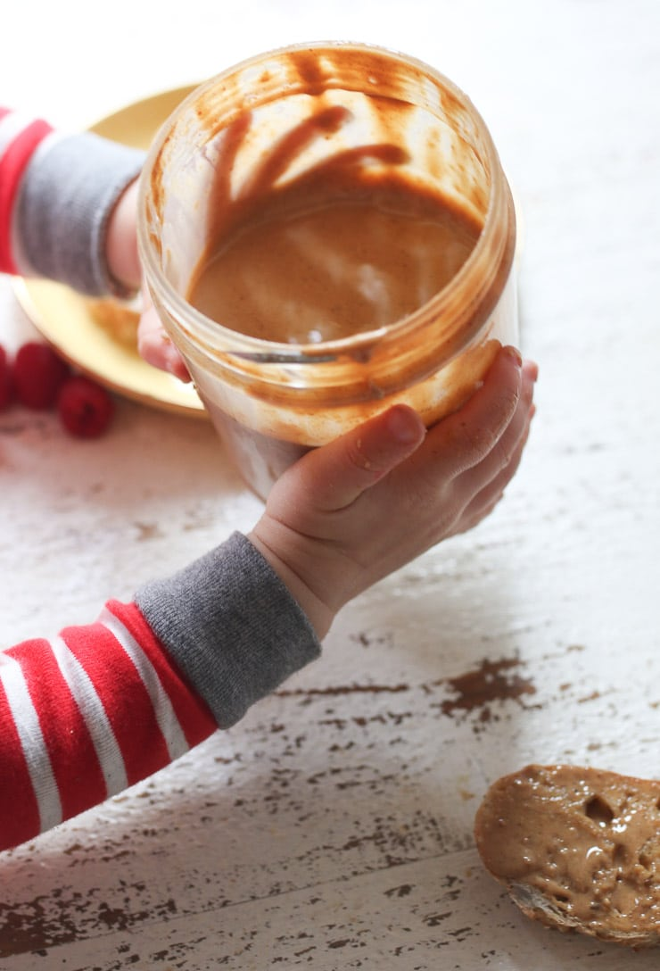 Baby's hand holding jar of peanut butter.