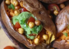 Guacamole and chickpeas stuffed sweet potato served on a wooden plate.