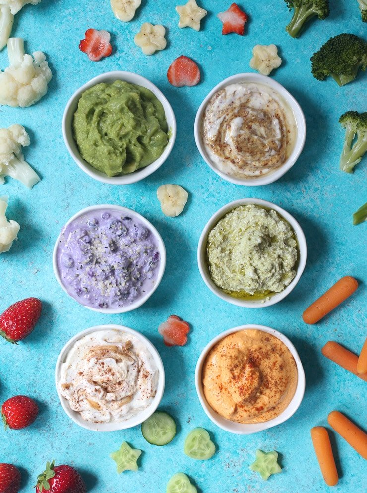 birds eye view of a variety of different dips in small white bowls for toddlers surrounded by fruits and vegetables