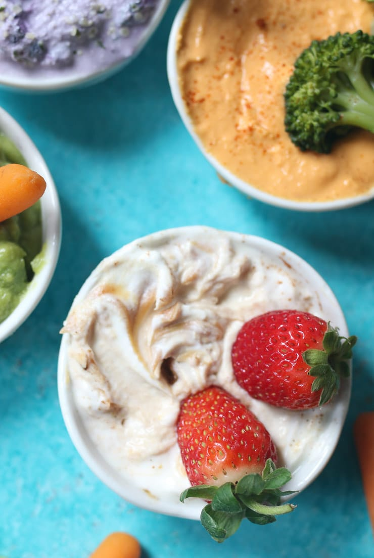 close up image of three varieties of dips for toddlers garnished with fruits and vegetables in small white bowls on a blue background