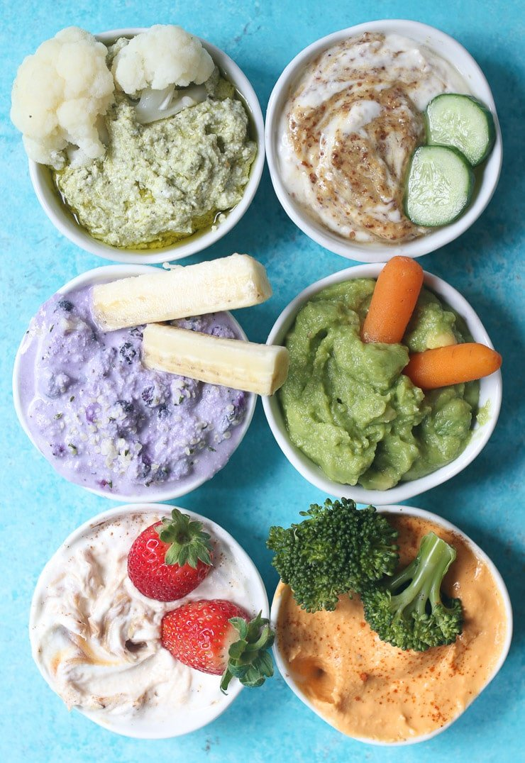 birds eye view of six different dips for toddlers in small white bowls garnished with fruits and vegetables