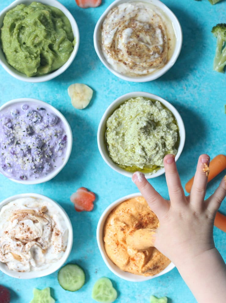 toddler hands dipping into a variety of dips.