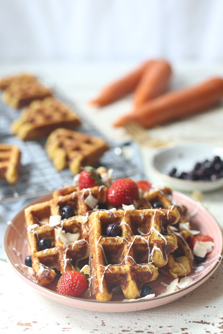 Carrot cake waffles topped with berries on pink plate.