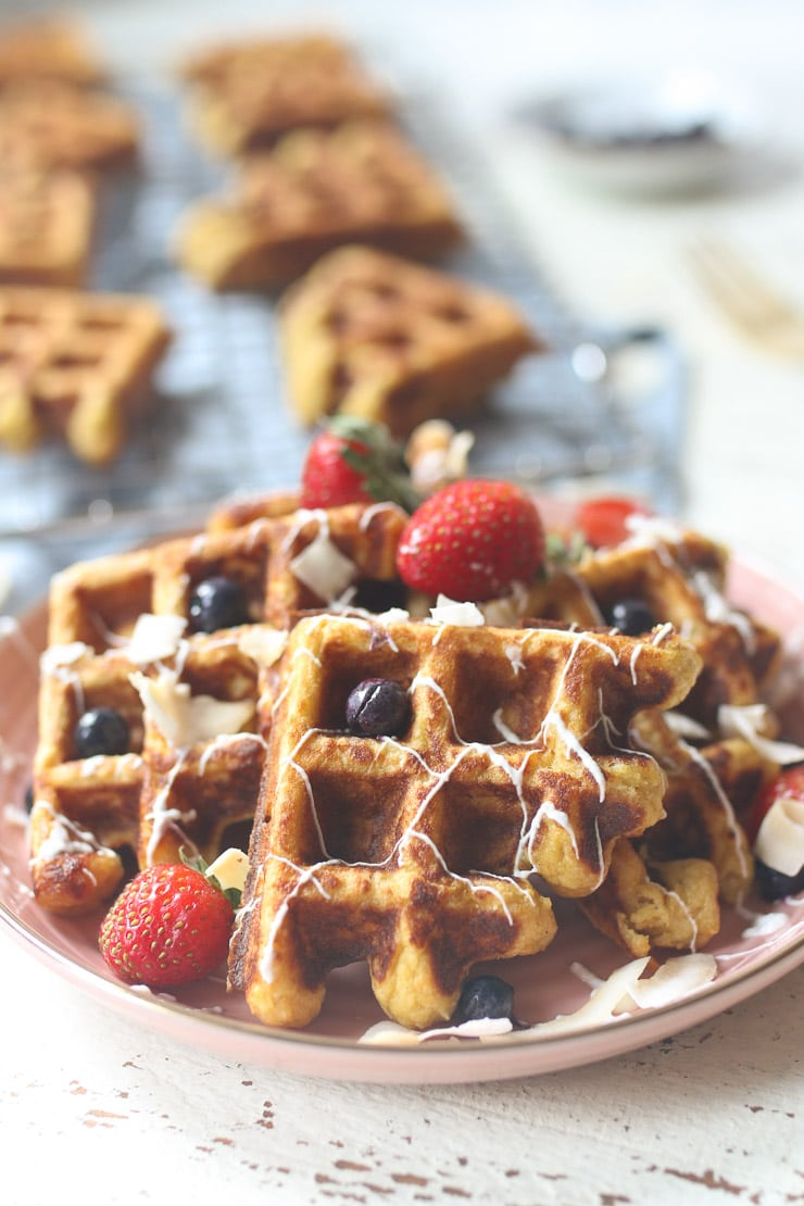 Carrot cake waffles served on a pink plate topped with berries.