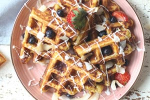 Waffles served on a pink plate topped with berries.