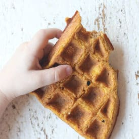 Toddler holding waffle.