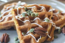 Waffles on a grey plate topped with pumpkin seeds and pecans.