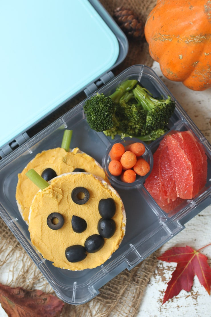 Rice cakes topped with hummus in a lunchbox.
