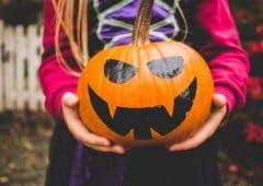 Girl holding pumpkin.