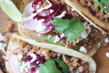 Three tacos on a wooden plate.