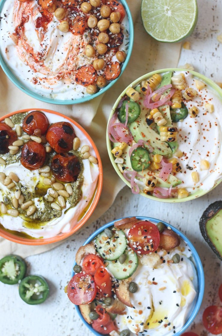 Four yogurt bowls with various savoury toppings.