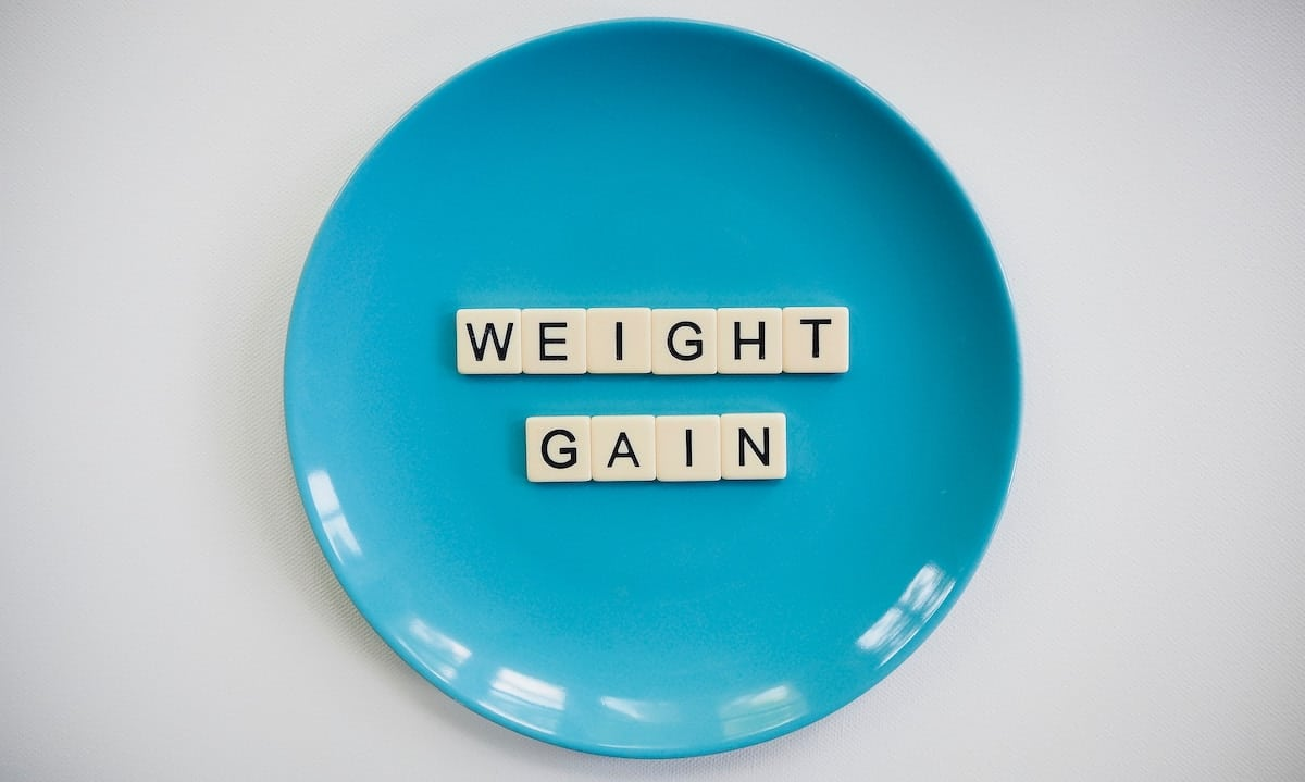 Plate with tiles that spell the word the word: weight gain.