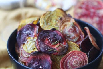 Crispy colourful beet chips in a black bowl.