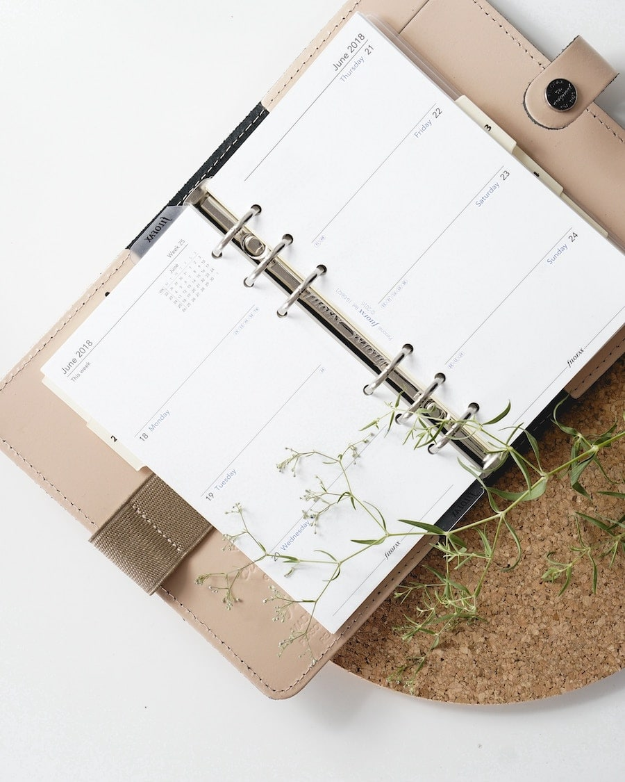 Overhead image of an opened beige and brown filofax planner.
