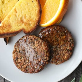 Two vegan breakfast sausage patties next to orange slices and toast on a plate.