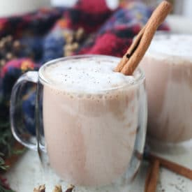 Egg nog in a glass mug topped with a cinnamon stick.