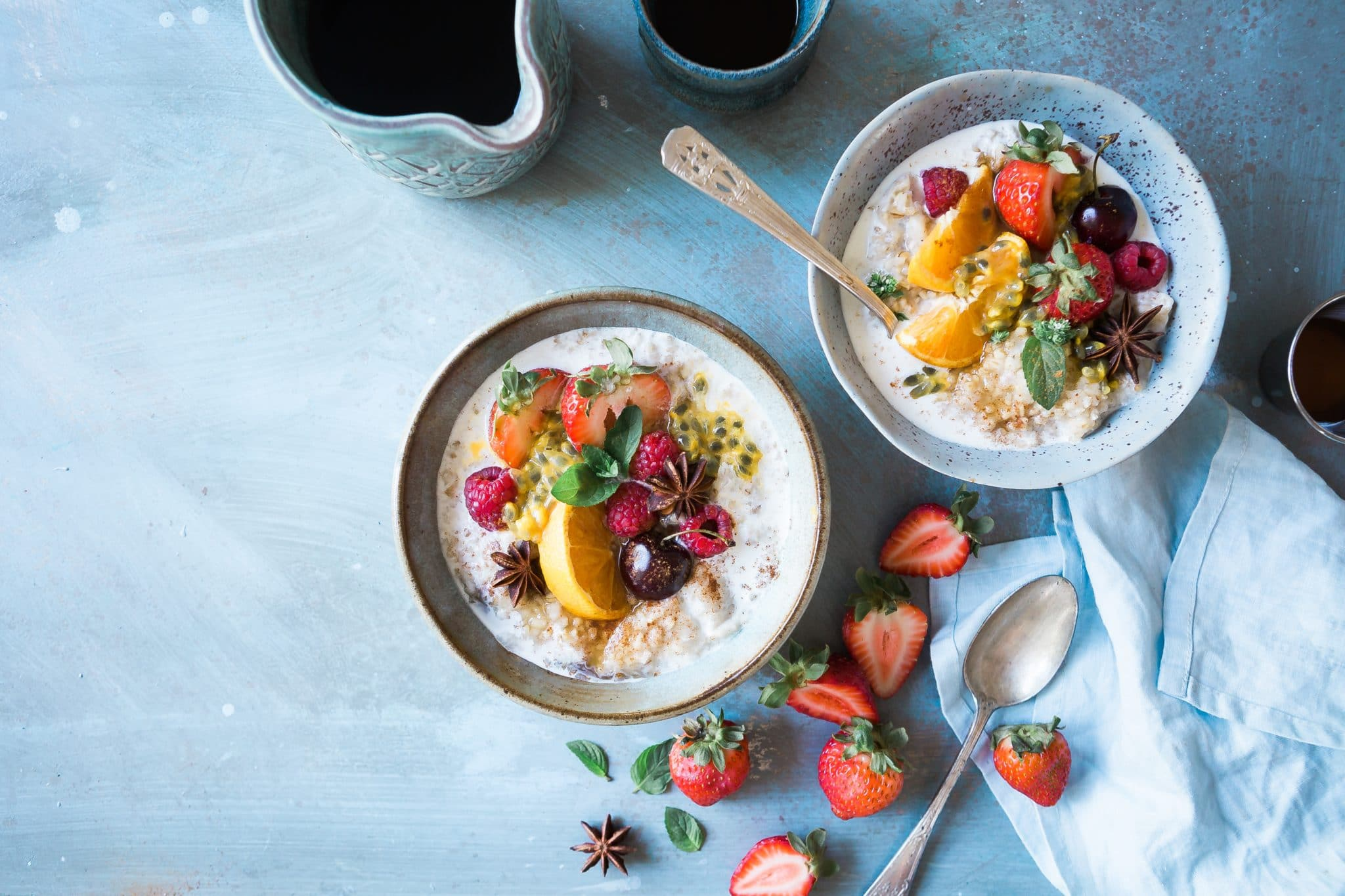 Two bowls of yogurt topped with a variety of fruit.