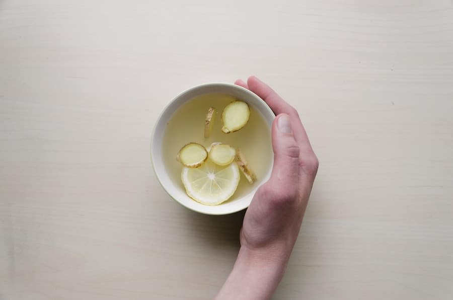 Hand holding mug of hot water with lemon and ginger.