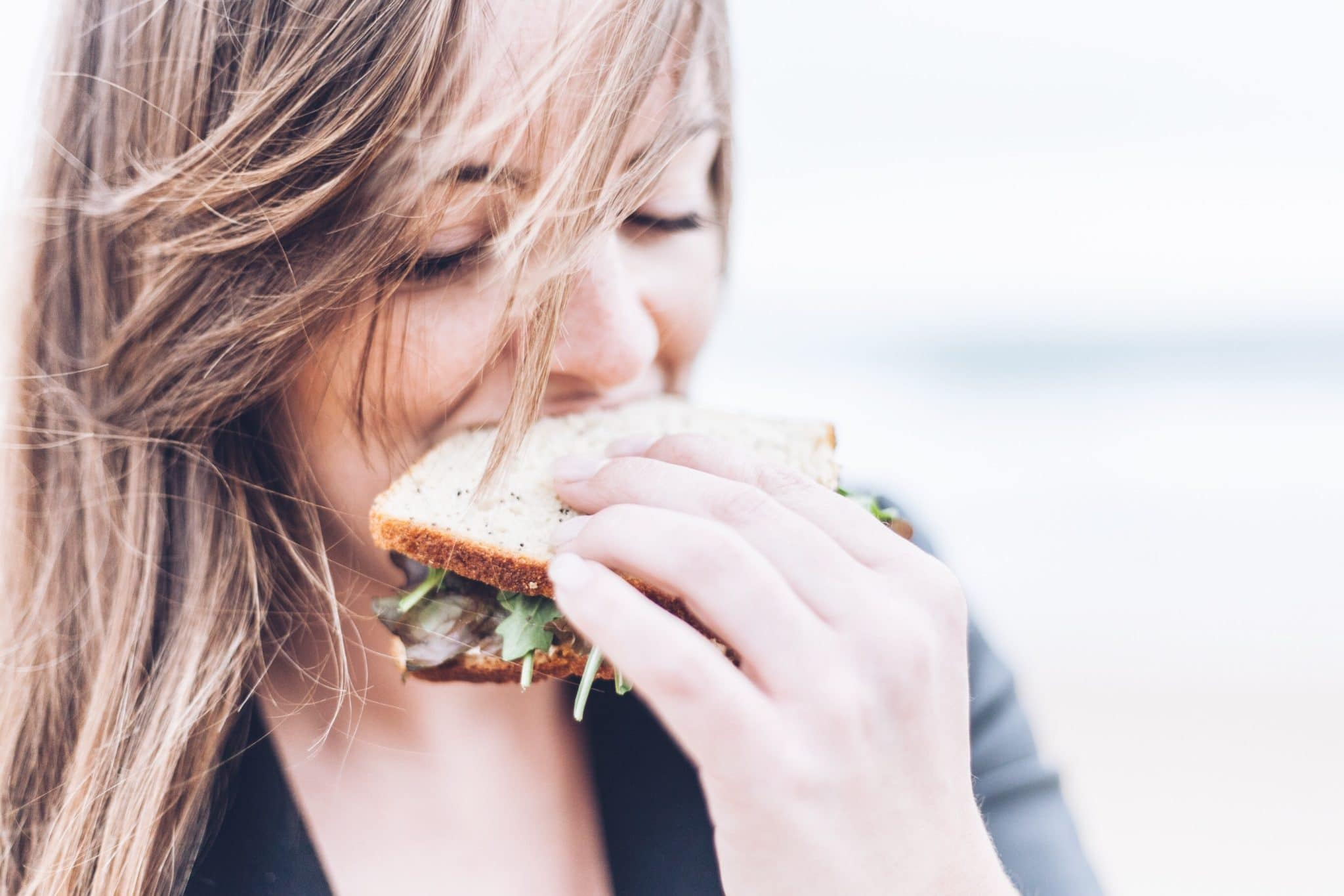 woman with PCOS taking a bite out of sandwich
