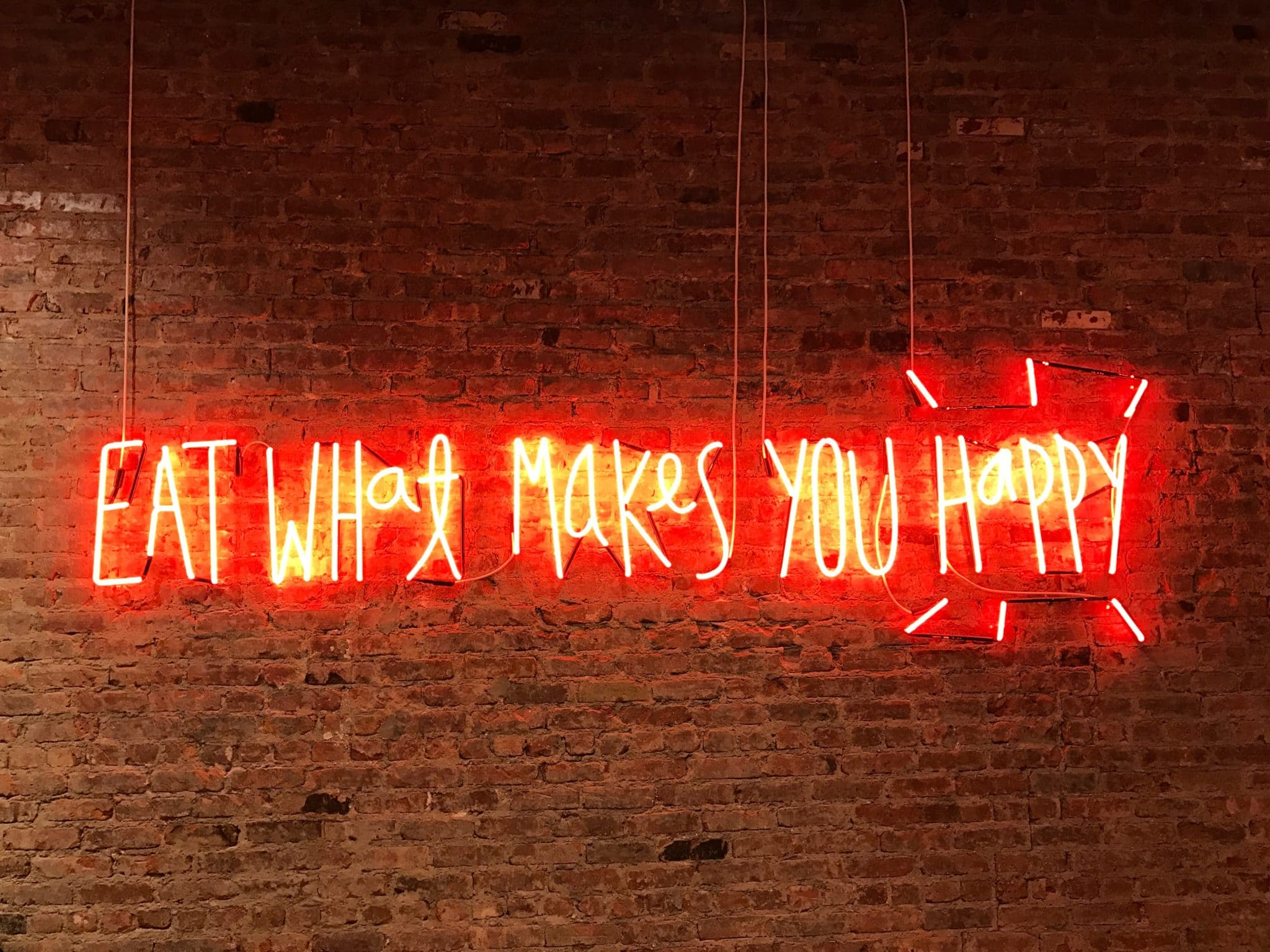 """""""eat what makes you happy"""" in lights written on a brick wall"""