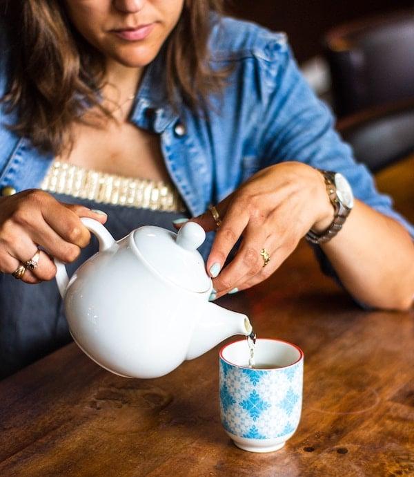 Person pouring tea into a mug.