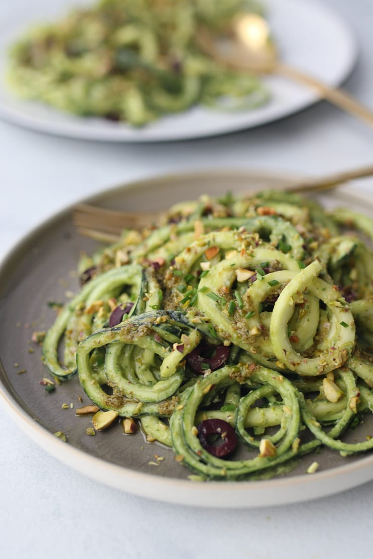 Avocado zucchini zoodles on a grey plate.